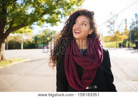 Photo of cheerful young dark skinned curly lady wearing scarf against nature background. Look aside.