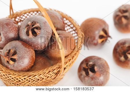 Raw common medlar fruits in the basket. Healthy food.
