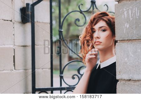 portrait of a beautiful woman with dark red hair, dressed in black, with a white collar. outside, with natural light. hairstyle and make-up in grunge style