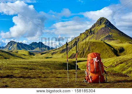 backpack and Trekking Poles on the trail in the Islandic mountains. Trek in National Park Landmannalaugar, Iceland. valley is covered with bright green moss