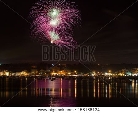 Fireworks. Colorful different amazing fireworks in dark sky background and house light in the far in Marsaxlokk, Malta fireworks festival, 4 of July, Independence day, New Year, maltese