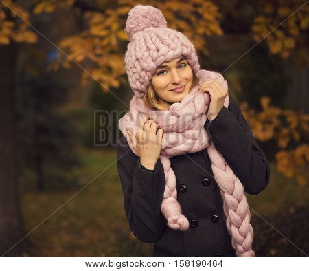 Beautiful young woman wearing merino wool pastel colors hat and scarf enjoying the fresh morning outdoors