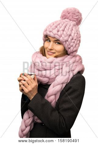 Smiling beautiful young woman wearing merino wool pastel colors hat and scarf with a cup of coffee isolated on white