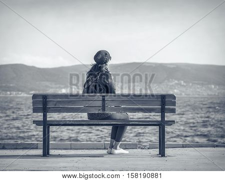 Woman sitting on the bench near the sea. Toned photo.