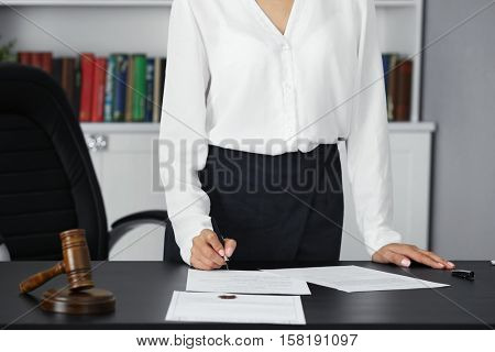 Woman signing important documents in modern office