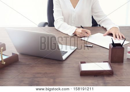 Female lawyer signing documents in office
