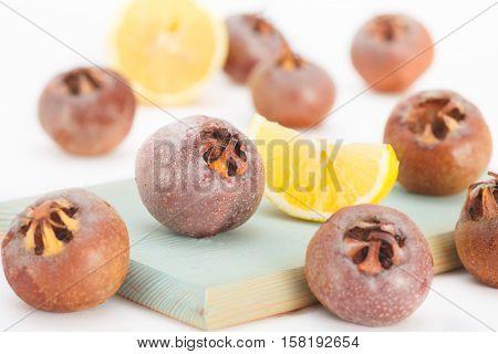 Healthy ripe Medlar fruit with lemon on blue wooden board