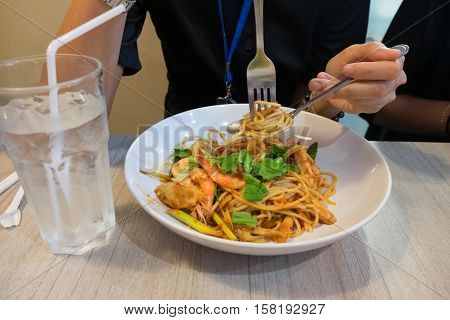 The spaghetti seafood. close up hand woman eating spaghetti with fork.
