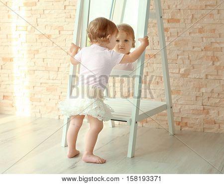 Little princess in beautiful dress posing near the mirror
