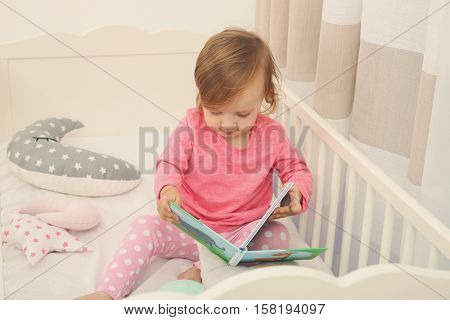 Cute little girl with book in cradle at baby room
