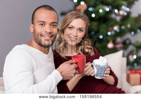 It is tea time. Handsome positive good looking man holding a red cup and looking at you while having tea