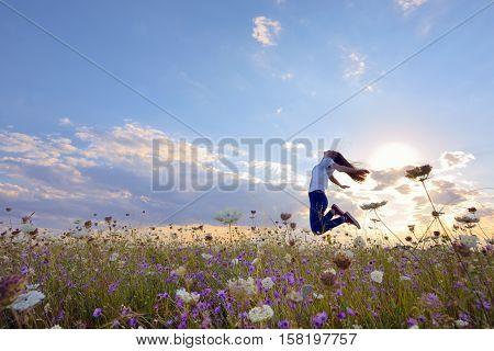Beautiful teenage girl jumping on summer field