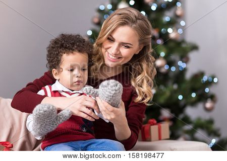 Being together. Delighted caring beautiful mother having her son on her lap and wearing a mitten on his hand while having fun together