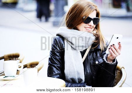 Young woman sitting at the street café , drinking coffee  and using mobile phone  with street life in winter time. Lifestyle concept