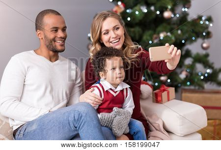 Family photo. Nice happy young family sitting together on the sofa and smiling while posing for a photo