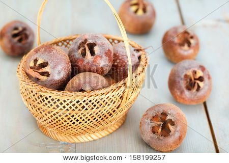 Healthy ripe Medlar fruit in basket and on blue wooden board