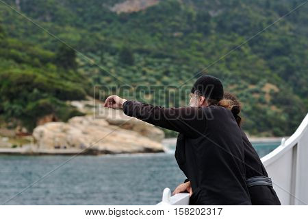 Holy mountain Greece - May 27 2015 : Monk s on a ferry while going to monastiry. Tourists from all over the world visit Holy mountain although women are not allowed to enter.