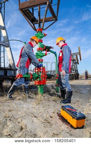 Workers in the oilfield one repairing wellhead with the wrench other supervising. Pump jack and wellhead background. Oil and gas concept.