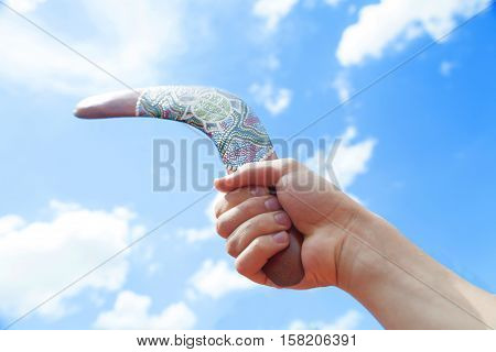 Wooden Boomerang with Blue Sky and Cloud Background