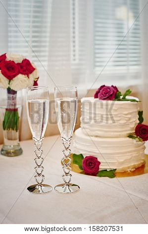 two glasses of champagne and wedding cake on the table.