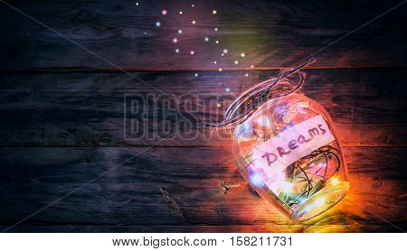 garlands colorful lights in glass jar with dreams sparks on old wooden table retro toned