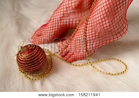 Female Feet In Red Stockings Wrapped With Gold Beads