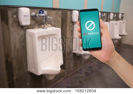 human hand hold smartphone tablet cell phone with blank screen on blurry row of urinal at public restroom.