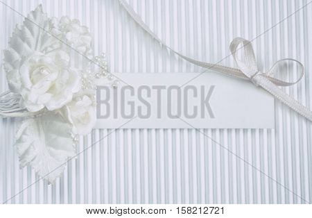 tender boutonniere blank tag white silk ribbon bow on fluted paper wedding card