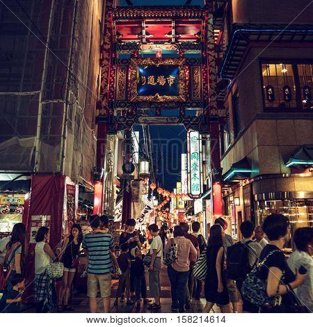 Yokohama - June 2016: Night street view with people and colorful wooden gate at Yokohama Chinatown.