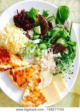 Golden cooked quiche with cheese and salad