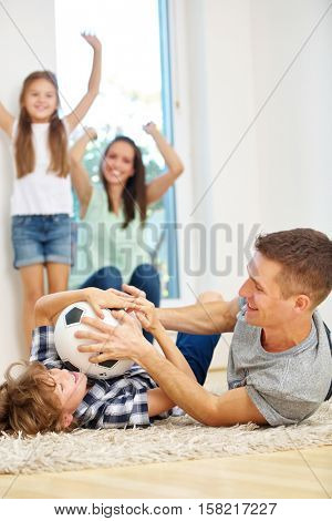 Happy family with two kids romping with soccer ball at home in the living room