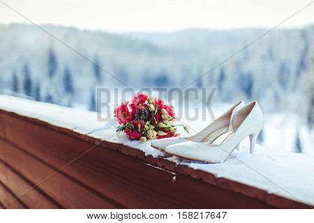 An elegant wedding bouquet of freesia, rose, eucalyptus in white and violet tones. Boutonniere on a wooden background. View from above