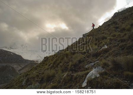 Hiker gazing at the glacier in the glacial valley in the desolate peruvian mountain landscape
