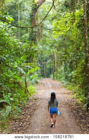 Woman walking in a jungle path in the Ko Kood island in Thailand