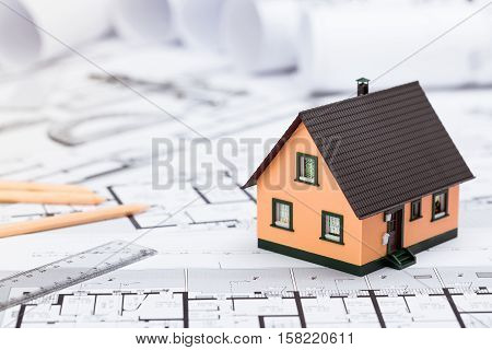 Construction Plans With Drawing Tools And House Miniature On Blueprints