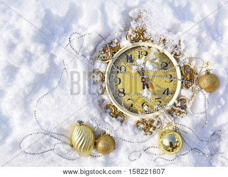 Christmas clock and Christmas decorations on the snow
