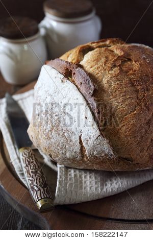 French country bread on dark wooden chopping board