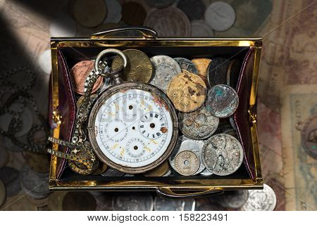 Open purse with old coins and a broken pocket watch without clock hands