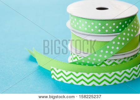Rolls of gift ribbon stacked on a blue background