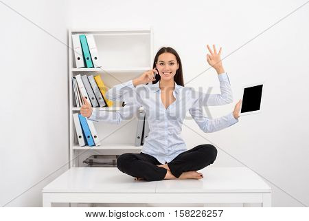 Smiling busy successful business woman multitasking in the office while sitting on the table