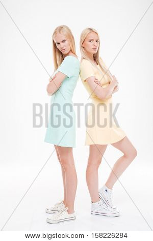 Photo of two indignant ladies standing back to each other with arms crossed over white background. Looking at the camera.