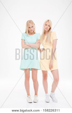 Photo of two indignant ladies posing over white background. Looking at the camera.
