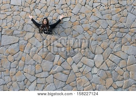 woman in layer of stone rock wall look back lift hands up in black and white dress happy face / woman and stone wall