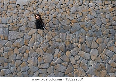 woman in layer of stone rock wall look back with curiosity in black and white dress happy face / woman and stone wall