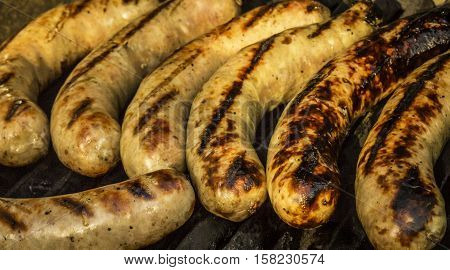 Large plump link sausages sizzling on a grill