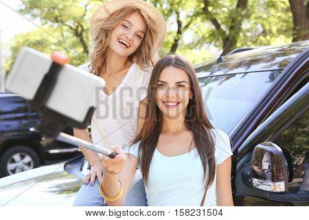 Happy friends taking selfie near car