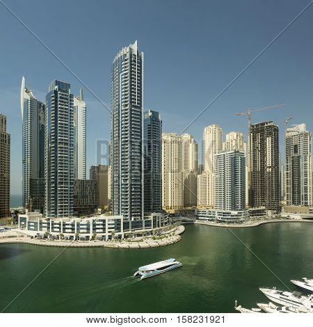 DUBAI UAE - NOVEMBER 7 2016: Luxury scyscrapers and yachts in Marina Dubai Unidet Arab Emirates. Dubai Marina in a summer day United Arab Emirates. Travel and advertising concept.