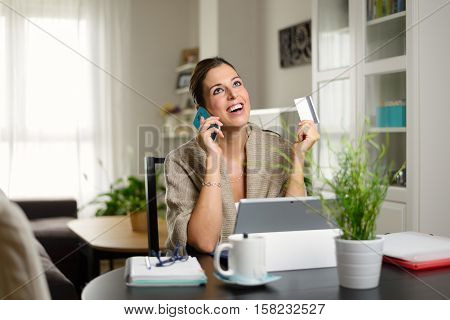 Happy woman doing online shopping on laptop at home. Cheerful female holding credit card and calling on cellphone.