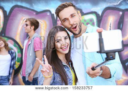 Happy friends taking selfie on street