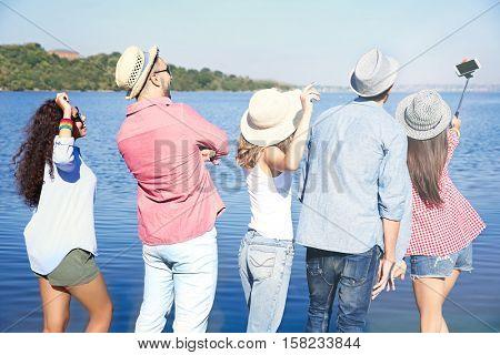 Happy friends taking selfie on beach